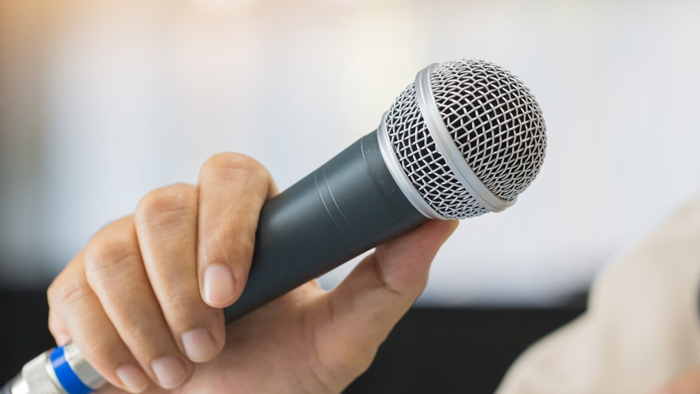 Man holding a microphone - signifies the different types of public speaking