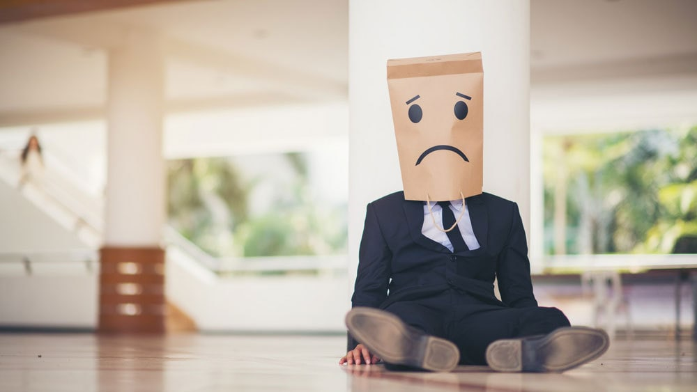 sad entrepreneur with no career growth wearing a bag over his head