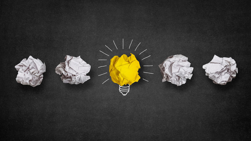 idea light bulb made out of yellow and white paper